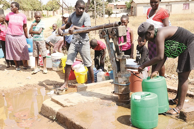 Nketa residents affected by water cuts queue to fetch the precious liquid from a borehole yesterday