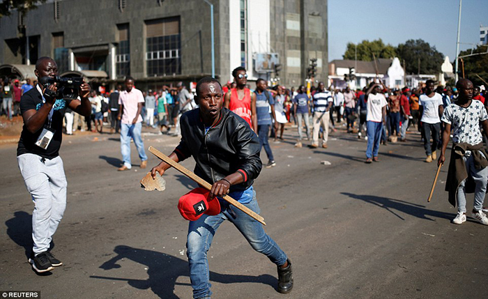 Automatic gunfire was heard in the capital Harare today while smoke has been seen rising from burning vehicles and pictures show trucks carrying security forces through the streets amid unrest
