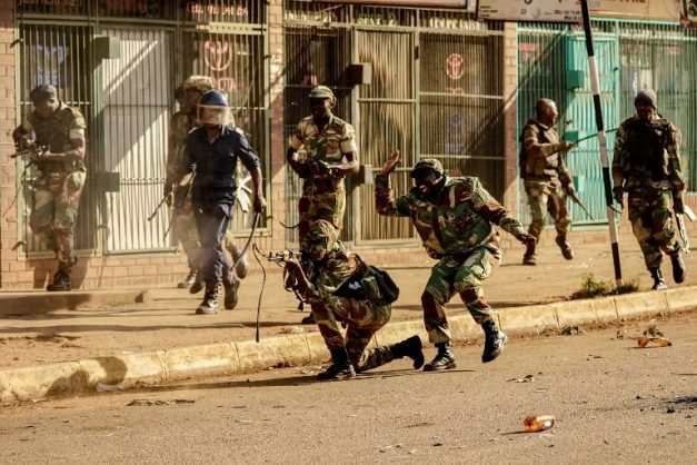 A soldier fires shots towards demonstrators, on August 1 2018, in Harare, as protests erupted over alleged fraud in the country's election. Protests in Zimbabwe's historic elections turned bloody on August 1 as a man was shot dead during demonstrations over alleged vote fraud and the president appealed for calm. The man died after soldiers fired live ammunition during opposition protests in downtown Harare, AFP reporters saw. / AFP PHOTO / Zinyange AUNTONY