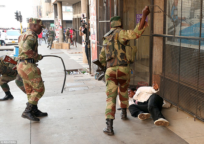 Violence: Shocking pictures show an opposition supporter being beaten in the streets of Harare by Zimbabwean soldiers