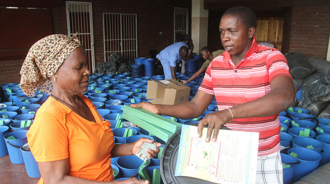 Mrs Olivia Nyuke (left) from Glen View 8 receives water containers, bars of washing soap and water treating tablets from Mr Collin Bacha at Glen View 1 Hall in Harare yesterday. The non-food items were donated by Unicef to residents in cholera-affected suburbs and distributed by Oxfam. — Picture by Kudakwashe Hunda