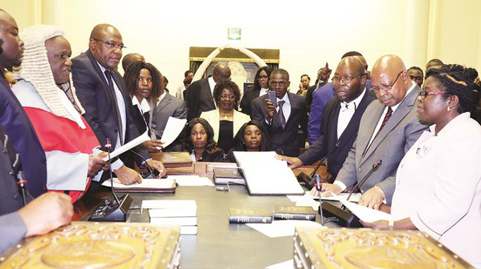 Speaker of Parliament Advocate Jacob Mudenda and his deputy Tsitsi Gezi (right) take their oath of office before Chief Justice Luke Malaba (left and wearing judicial robe) in Parliament. — Picture by Tawanda Mudimu