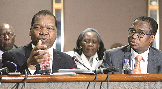 Reserve Bank of Zimbabwe Governor Dr John Mangudya (left) makes an address during the mid-term monetary policy presentation in Harare as Minister of Finance and Economic Development, Professor Mthuli Ncube listens