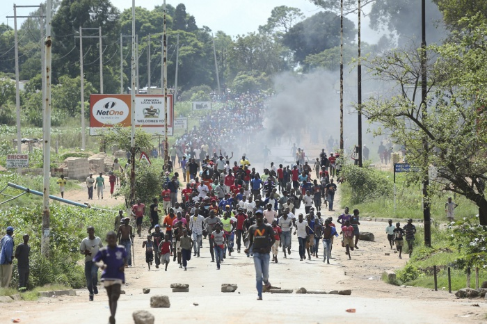 Protestors gather on the streets during demonstrations over the hike in fuel prices in Harare, Zimbabwe, Monday, Jan. 14, 2019.  Protesters have blocked roads in some parts in Zimbabwe's capital after the government more than doubled the price of gasoline. (AP Photo/Tsvangirayi Mukwazhi)