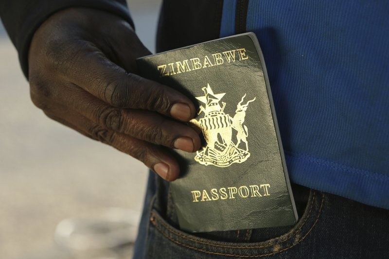 A man puts an expired passport in his pocket while waiting in a queue to submit an application for a new passport at the main office in Harare, Friday, June 14, 2019. With Zimbabwe's economy in shambles and political tensions rising, leaving the country seems the best option for many who are desperate for jobs. But those dreams often end at the passport office, which doesn't have enough foreign currency to import proper paper and ink. (AP Photo/Tsvangirayi Mukwazhi)
