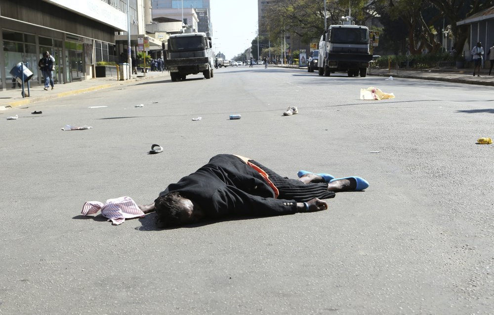 A woman lies in the road after been injured by police during protests in Harare, Friday, Aug, 16, 2019. The main opposition Movement For Democratic Change party is holding protests over deteriorating economic conditions in the country as well as to try and force Zimbabwean President Emmerson Mnangagwa to set up a transitional authority to address the crisis and organize credible elections. (AP Photo/Tsvangirayi Mukwazhi)