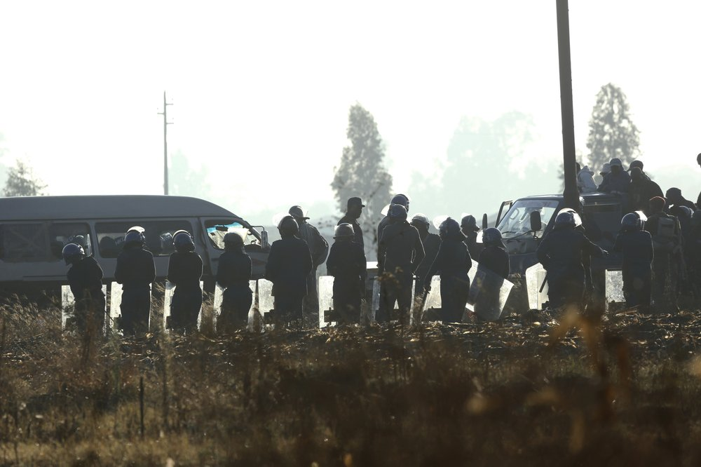 Armed riot police gather at a check point ahead of a planned protest in Harare, Friday, Aug. 16, 2019. Zimbabwe's police patrolled the streets of the capital Friday morning while many residents stayed home fearing violence from an anti-government demonstration planned by the opposition. (AP Photo/Tsvangirayi Mukwazhi)
