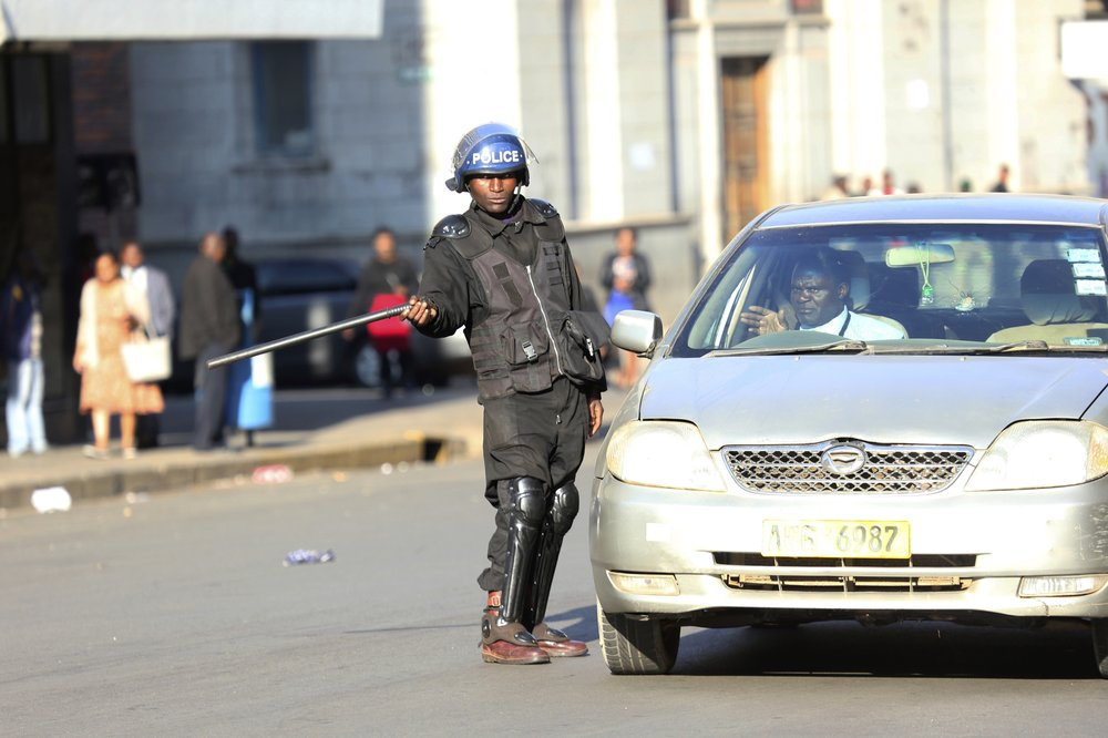 A riot police gives direction to a driver in Harare, Friday, Aug. 16, 2019. Zimbabwe's police patrolled the streets of the capital Friday morning while many residents stayed home fearing violence from an anti-government demonstration planned by the opposition. (AP Photo/Tsvangirayi Mukwazhi)