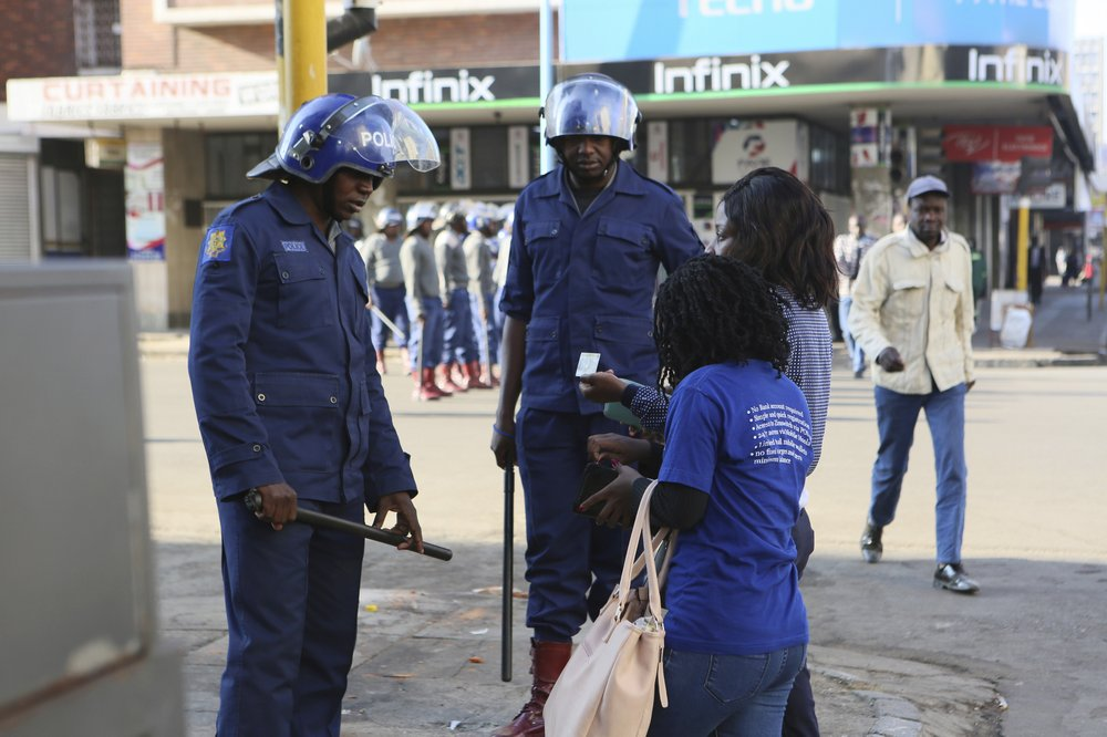 A woman shows her identity card to a police officer in Harare, Friday, Aug. 16, 2019. Zimbabwe's police patrolled the streets of the capital Friday morning while many residents stayed home fearing violence from an anti-government demonstration planned by the opposition. (AP Photo/Tsvangirayi Mukwazhi)