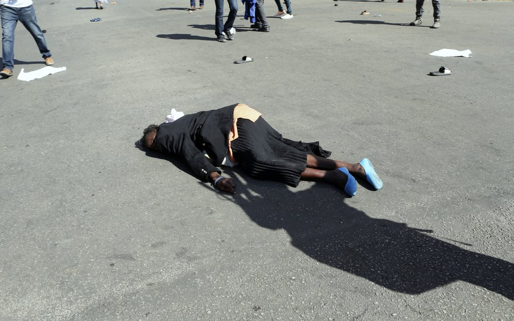A woman lies injured on the tarmac after been injured by police during protests in Harare, Friday, Aug. 16, 2019. Zimbabwe's police patrolled the streets of Harare Friday morning while many residents stayed home and shops were shut fearing violence from an anti-government demonstration. Zimbabwe's High Court has upheld the police ban on the opposition protest. (AP Photo/Tsvangirayi Mukwazhi)