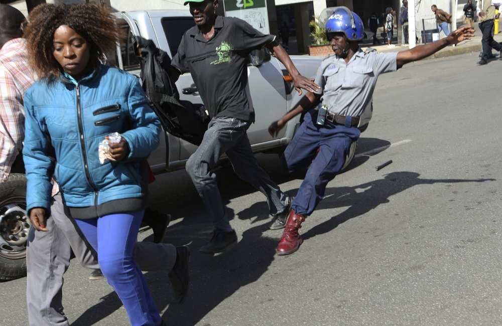A riot police man kicks out at a man during protests in Harare, Friday, Aug. 16, 2019. The main opposition Movement For Democratic Change party is holding protests over deteriorating economic conditions in the country as well as to try and force Zimbabwean President Emmerson Mnangagwa to set up a transitional authority to address the crisis and organize credible elections. (AP Photo/Tsvangirayi Mukwazhi)