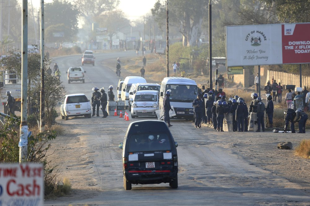 Police stop and search vehicles at a check point ahead of a planned protest in Harare, Friday, Aug. 16, 2019.. Zimbabwe's police patrolled the streets of the capital Friday morning while many residents stayed home fearing violence from an anti-government demonstration planned by the opposition. (AP Photo/Tsvangirayi Mukwazhi)