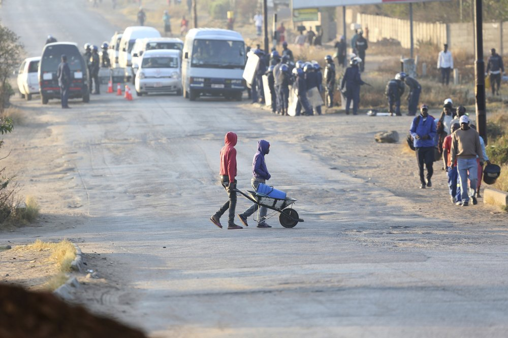 People cross a road with a wheelbarrow near a police check point ahead of a planned protest in Harare, Friday, Aug. 16, 2019.. Zimbabwe's police patrolled the streets of the capital Friday morning while many residents stayed home fearing violence from an anti-government demonstration planned by the opposition. (AP Photo/Tsvangirayi Mukwazhi)