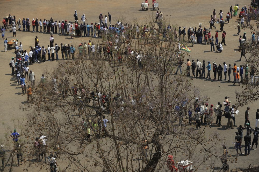 People queue at the Rufaro Stadium in Harare, Thursday, Sept. 12, 2019, where former President Robert Mugabe will lie in state for a public viewing. The body of the former guerrilla leader is to be on view at several historic sites in the next few days but where and when he will be buried has not been announced. (AP Photo/Themba Hadebe)