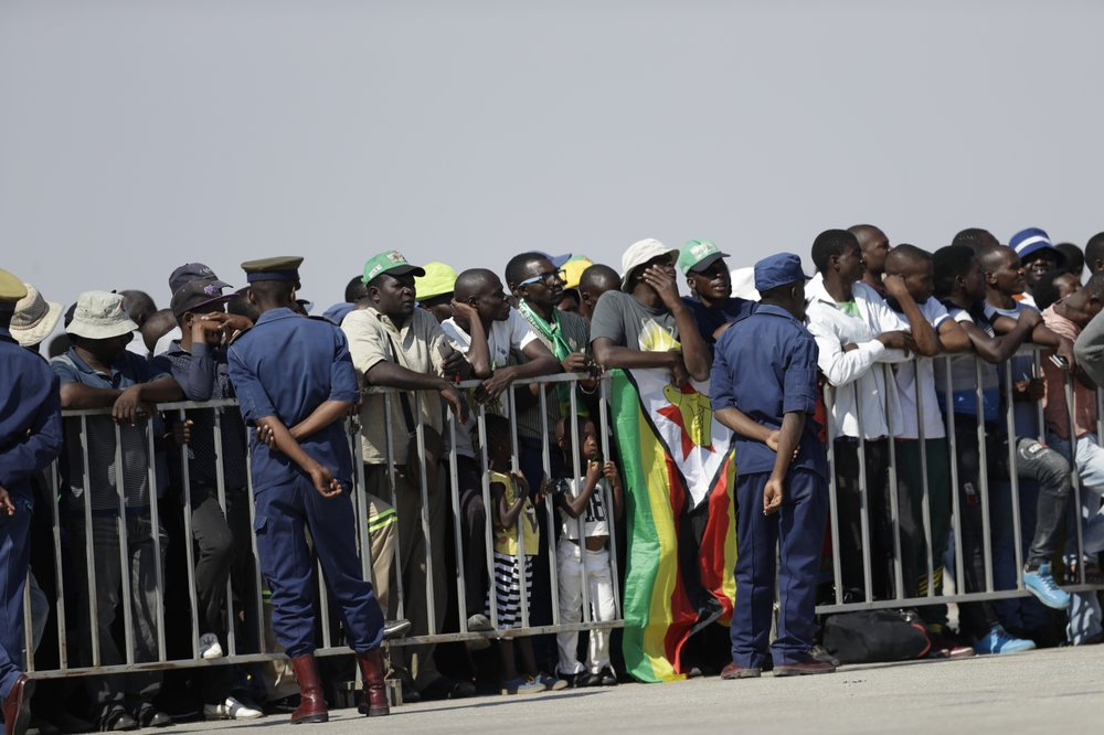 Zimbabweans await for the arrival of the body of Zimbabwe's longtime ruler Robert Mugabe from Singapore, at the RG Mugabe International Airport in Harare, Wednesday Sept. 11, 2019. The body of Mugabe is being flown to the capital, Harare, on Wednesday where it will be displayed at historic locations for several days before burial at a location still undecided because of friction between the ex-leader's family and the government. (AP Photo/Themba Hadebe)