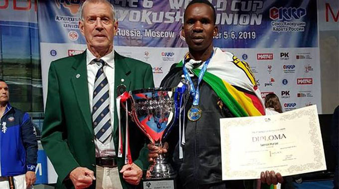 Zimbabwean karateka Samson Muripo holds his trophy and certificate in the company of Shihan Bas van Stenis after winning the world championship in Moscow, Russia, at the weekend