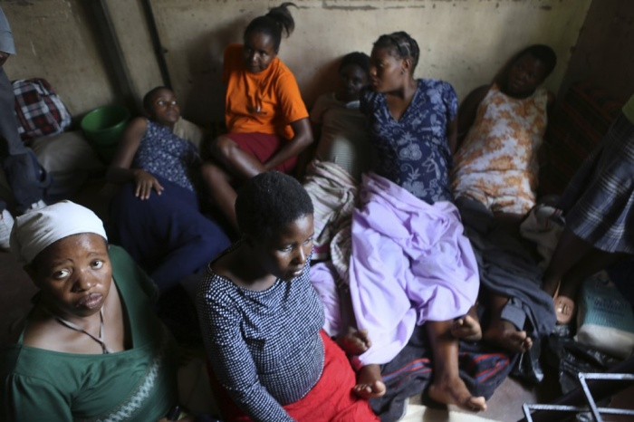 Women wait for their turn to deliver their babies, in a cramped apartment in the poor suburb of Mbare in Harare, Zimbabwe, Saturday, Nov. 16, 2019, with the help of 72-year old grandmother Esther Zinyoro Gwena. Grandmother Esther Zinyoro Gwena claims to be guided by the holy spirit and has become a local hero, as the country's economic crisis forces closure of medical facilities, and mothers-to-be seek out untrained birth attendants.(AP Photo/Tsvangirayi Mukwazhi)