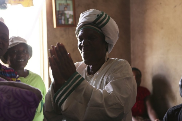72-year old grandmother Esther Zinyoro Gwena is seen in her a tiny apartment in the poor surburb of Mbare in Harare, Zimbabwe in this Saturday, Nov. 16, 2019. Grandmother Esther Zinyoro Gwena claims to be guided by the holy spirit and has become a local hero, as the country's economic crisis forces closure of medical facilities, and mothers-to-be seek out untrained birth attendants.(AP Photo/Tsvangirayi Mukwazhi)