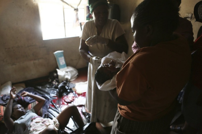 A woman holds a baby delivered in a tiny apartment in the poor suburb of Mbare in Harare, Zimbabwe, Saturday, Nov. 16, 2019, after the baby was delivered with the help of 72-year old grandmother Esther Zinyoro Gwena. Grandmother Esther Zinyoro Gwena claims to be guided by the holy spirit and has become a local hero, as the country's economic crisis forces closure of medical facilities, and mothers-to-be seek out untrained birth attendants.(AP Photo/Tsvangirayi Mukwazhi)