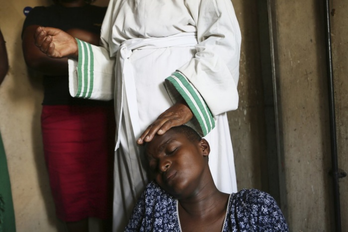 Esther Zinyoro Gwena comforts a woman in labor, in her tiny apartment in the poor suburb of Mbare in Harare, Zimbabwe in this Saturday, Nov, 16, 2019. 72-year old grandmother Esther Zinyoro Gwena claims to be guided by the holy spirit and has become a local hero, as the country's economic crisis forces closure of medical facilities, and mothers-to-be seek out untrained birth attendants.(AP Photo/Tsvangirayi Mukwazhi)