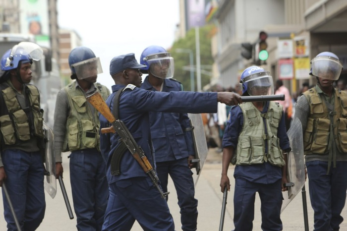 Police officers stand by as opposition party supporters gathered to hear a speech by the country's top opposition leader in Harare, Wednesday, Nov, 20, 2019. Zimbabwean police with riot gear fired tear gas and struck people who had gathered at the opposition party headquarters to hear a speech by the main opposition leader Nelson Chamisa who still disputes his narrow loss to Zimbabwean President Emmerson Mnangagwa. (AP Photo/Tsvangirayi Mukwazhi)