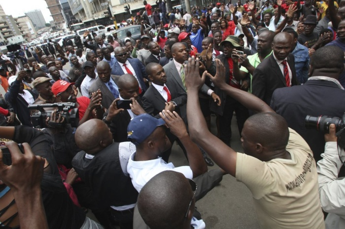 Zimbabwe top opposition leader Nelson Chamisa, center, arrives to deliver his speech at the party headquarters in Harare, Wednesday, Nov. 20, 2019. Zimbabwean police with riot gear fired tear gas and struck people who had gathered at the opposition party headquarters to hear a speech by the main opposition leader Nelson Chamisa who still disputes his narrow loss to Zimbabwean President Emmerson Mnangagwa. (AP Photo/Tsvangirayi Mukwazhi)