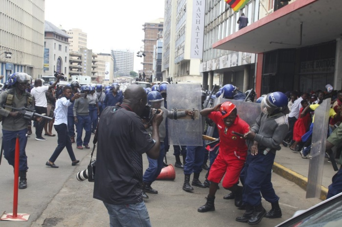 Police surround opposition party supporters who had gathered to hear a speech by the country's top opposition leader in Harare, Wednesday, Nov. 20, 2019. Zimbabwean police with riot gear fired tear gas and struck people who had gathered at the opposition party headquarters to hear a speech by the main opposition leader Nelson Chamisa who still disputes his narrow loss to Zimbabwean President Emmerson Mnangagwa. (AP Photo/Tsvangirayi Mukwazhi)