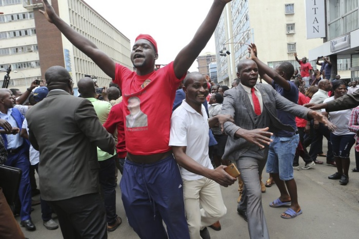 Opposition party suppoters sing and dance while waiting to hear a speech by the country's top opposition leader in Harare, Wednesday, Nov. 20, 2019. Zimbabwean police with riot gear fired tear gas and struck people who had gathered at the opposition party headquarters to hear a speech by the main opposition leader Nelson Chamisa who still disputes his narrow loss to Zimbabwean President Emmerson Mnangagwa. (AP Photo/Tsvangirayi Mukwazhi)