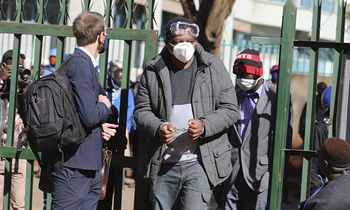 Zimbabwe journalist Hopewell Chin'ono appears at the magistrates courts while handcuffed in Harare, Wednesday, July, 22, 2020. Chin'ono known for exposing alleged government corruption is now accused of plotting against the government. Hopwell Chin'ono appeared alongside Jacob Ngarivhume, an opposition politician who is accused of conspiring with to mobilize anti government protests planned for July 31. (AP Photo/Tsvangirayi Mukwazhi)